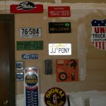 Lots of license plates and old porcelain signs